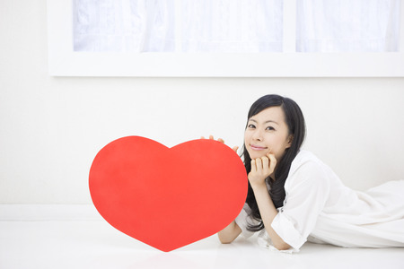 Women with heart-shaped board lying down Stock Photo