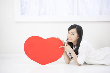 heartshaped: Women with heart-shaped board lying down Stock Photo