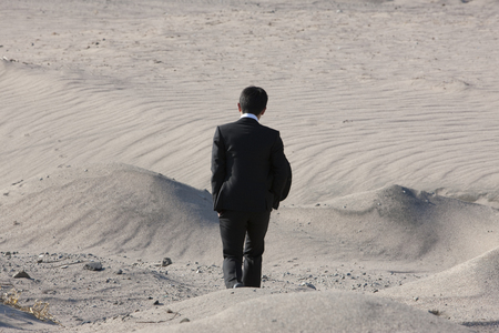 ambivalence: Businessman walking the desert