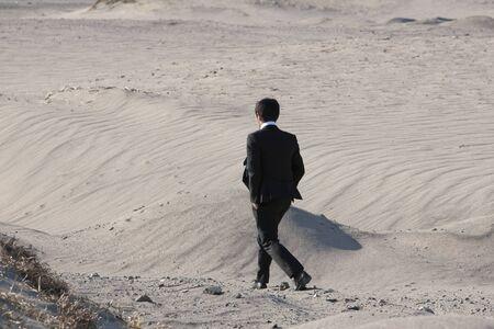 Businessman walking the desert