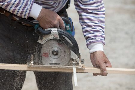 electric saw: Carpenters that use the electric saw Stock Photo