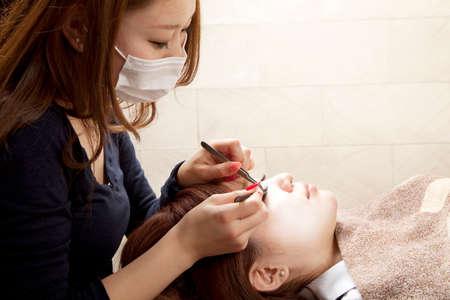 esthetician: Esthetician to the eyelashes extension Stock Photo