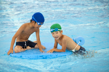 young boy in pool: Elementary school students playing by the pool boy Stock Photo