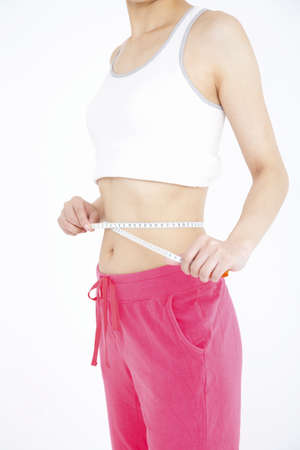 measuring waist: Hungry woman measuring waist size Stock Photo