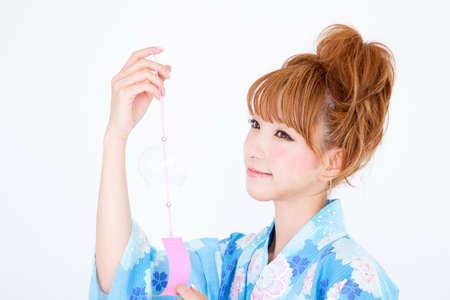 Women dressed in yukata have wind chimes photo