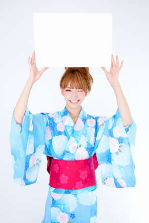 get dressed: Women dressed in yukata have message board Stock Photo