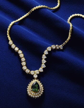 ブルー ベルベットのダイヤモンドとエメラルドのペンダントに入れられています。