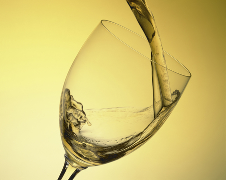 poured: White wine is poured into a wine glass