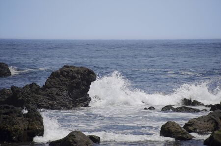 blue waters: Spindrift to crumble in the blue waters of the rocky Stock Photo