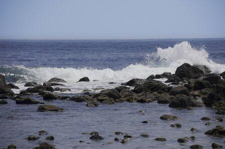 vigorous: Vigorous waves crashing splash in the blue waters of the rocky Stock Photo