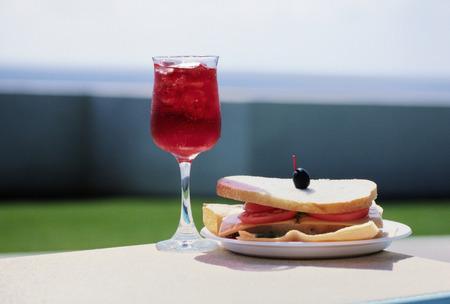 プール側からアセロラ ジュースとサンドイッチのローアングル 写真素材