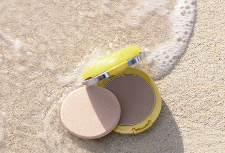 face powder: UV face powder that is placed in grazing wave of sandy beach Stock Photo