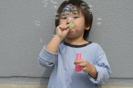 young fellow: Boy blowing soap bubbles towards the camera