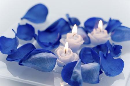 Candles and blue rose petals
