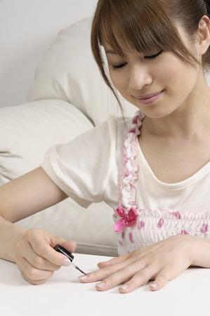 nailcare: Women apply Nail Polish Stock Photo