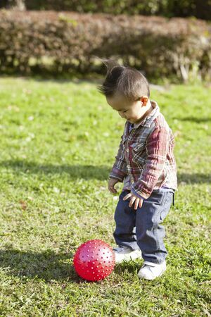 red ball: Little boy and a red ball Stock Photo