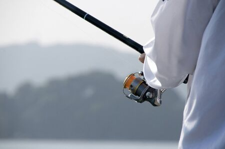 sea fishing: Hand holding a fishing rod Stock Photo
