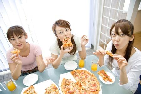 ピザを食べる女性 写真素材