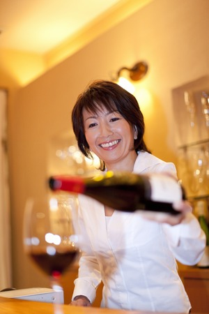 downlight: Womens sommelier pour wine into a glass