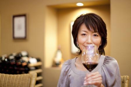 バーのカウンターでワインを飲んでいる女性