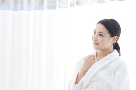 house robe: Women sit in the Salon bed Stock Photo