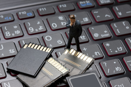memory card: Miniature businessmen to think by looking at the memory card Stock Photo