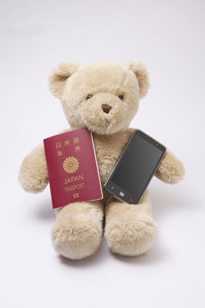 foreign country: Teddy bear with a passport and a smartphone