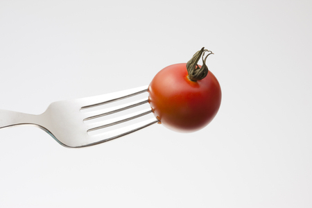 stabbed: Mini tomatoes stabbed to fork Stock Photo