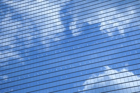 window  glass: Clouds reflected in the window glass of the building