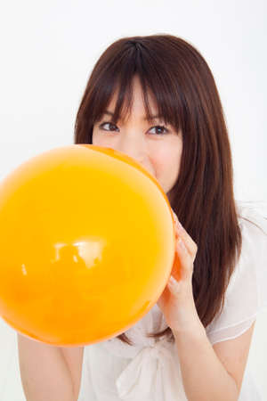 inflating: Woman inflating the balloon Stock Photo