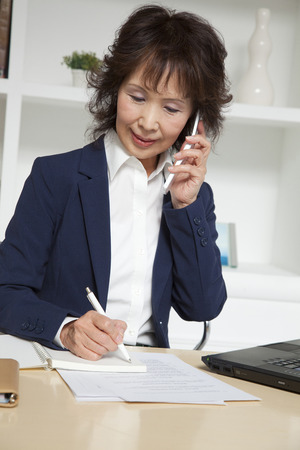exert: Businesswoman taking notes while phone