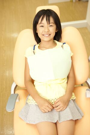 reclining chair: Girl sitting in the dentist reclining chair Stock Photo