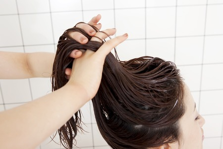 hair treatment: Hand of the hairdresser to put the treatment in women of hair