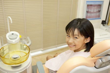 reclining chair: Girl look back to sit in the dentist reclining chair Stock Photo