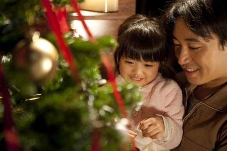 娘と父のクリスマス ツリーを飾る