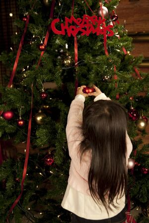 back shot: Back shot of a girl to the decorations of Christmas tree Stock Photo