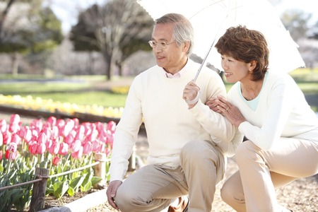 lean over: Senior couple to see the flower