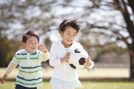 サッカー ボールを持って走っている少女 写真素材