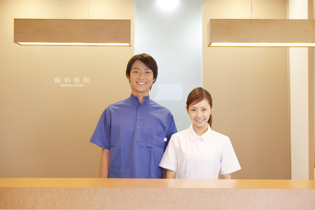 Dentist standing in reception and dental hygienists