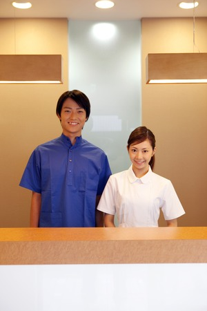 standing reception: Dentist standing in reception and dental hygienists