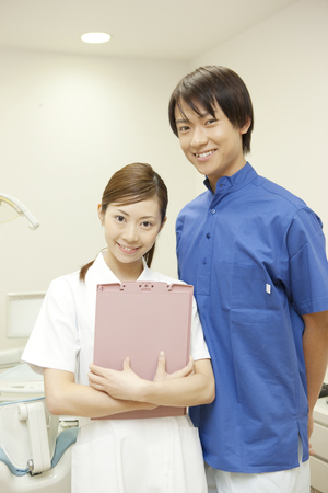 hygienist: Male dentist and dental hygienist standing in front of the treatment table