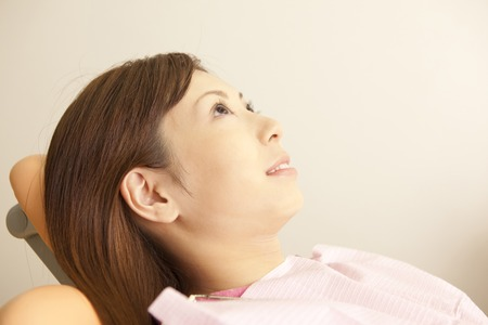 reclining chair: Women sit in a reclining chair of dentist Stock Photo