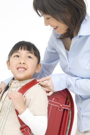 nuclear family: Daughter and mother carrying a school bag Stock Photo