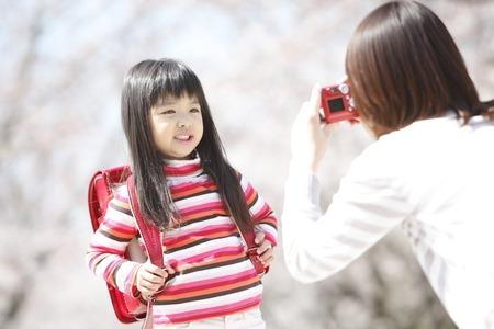 桜の木の下で小学生の女の子を撮影する母