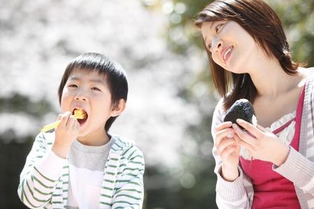 桜の木の下で昼食を食べに母と子