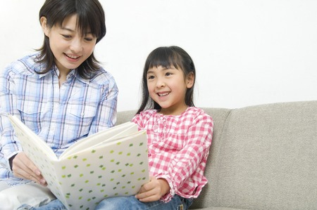 momma: Mother to hear read the book to her daughter Stock Photo