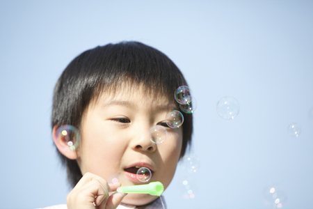 young fellow: Boy playing with soap bubbles Stock Photo