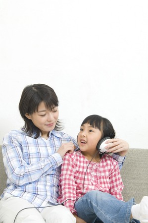 nuclear family: Daughter and mother to listen to music Stock Photo