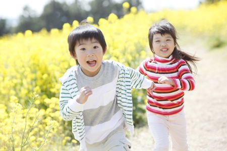 Male and female elementary school students running a rape field