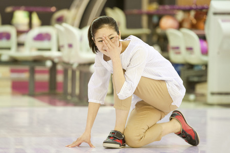 Woman covering the eyes with the bowling Banque d'images